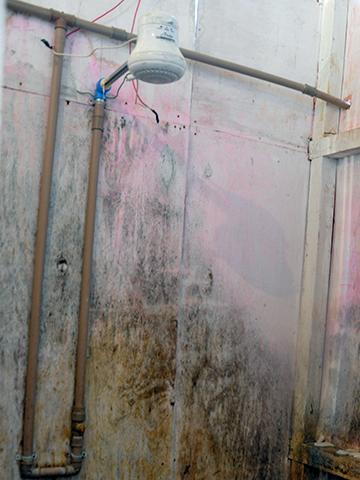 Chuveiro improvisado no abrigo em que o grupo estava alojado; fiação exposta oferecia riscos