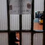 Porta com vidros quebrados e aviso em espanhol