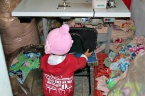 Criança em oficina onde foi registrado flagrante de trabalho escravo na produção de peças da grife Talita Kume.