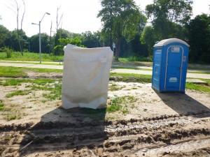 Anteparo construído para banho de trabalhador ao lado de banheiro químico em obra do Arraial da Lagoa