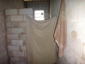 Banheiro improvisado de uma das casas, com divisória de lençol (Foto: SRTE-SP)