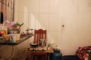 Cozinha de uma das casas: o fogão portátil comprado pelos trabalhadores ficava em cima de uma cadeira, ligado ao botijão de gás no pé do colchão de ar onde um deles dormia (Foto: Stefano Wrobleski)