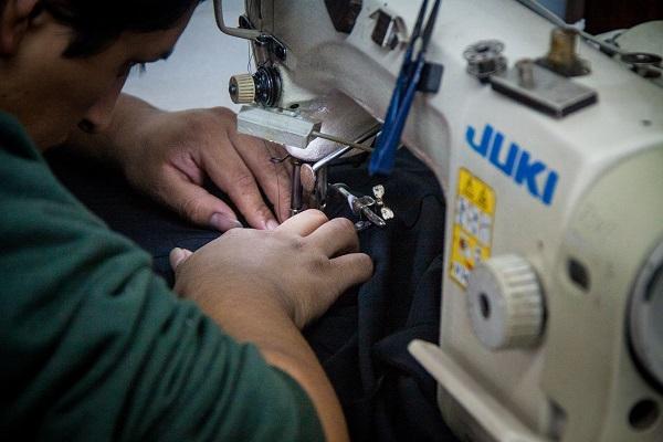 Pagos por produção, os trabalhadores resgatados em março deste ano continuaram costurando mesmo durante a fiscalização. Eles produziam para as grifes Emme, Cori e Luigi Bertolli  (Foto: Anali Dupré)
