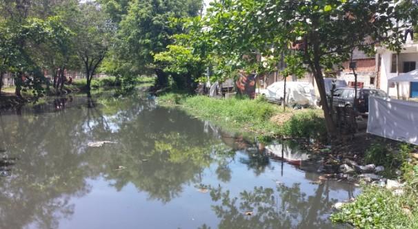 Entrada da favela Vila Autódromo, onde diversos trabalhadores moravam,com esgoto correndo a céu aberto