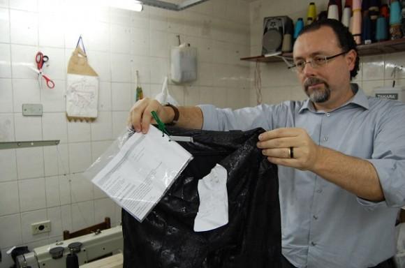 Deputado Carlos Bezerra Jr., presidente da CPI do Trabalho Escravo, segura calça da M. Officer encontrada oficina