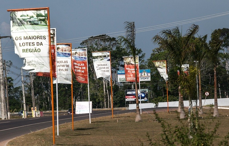 Placas e banners com propaganda imobiliária forram a estrada, na chegada à Iranduba. Foto: Lilo Clareto