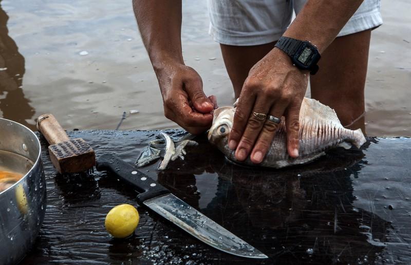 Mulher limpa o pescado no próprio Tapajós antes de levar o peixe para casa. Foto: Lilo Clareto/Reporter Brasil