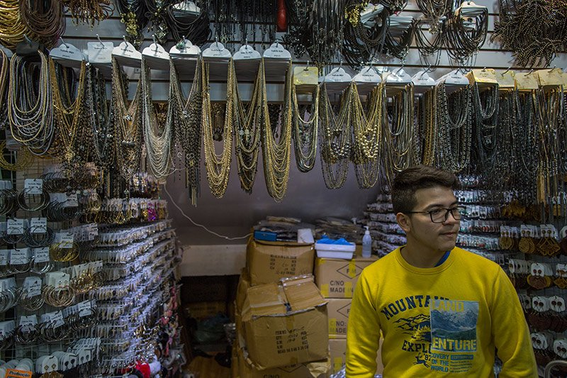 Gustavo Adolfo, 18 anos, nasceu no Paraguai e vive no Brasil desde os cinco. Em uma galeria da Feirinha, ele trabalha na banca do seu tio, que tem vários pontos de venda de bijuterias na cidade. Foto: Flavio Forner/The Guardian