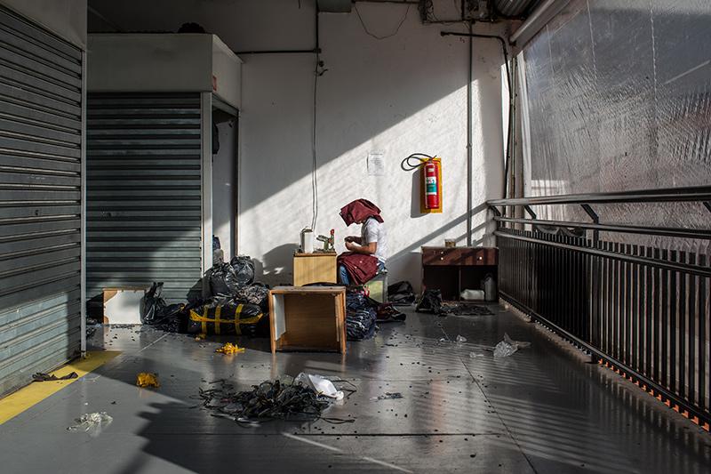 Depois que a polícia passa e os feirantes são obrigados a se retirar da rua, algumas galerias viram ponto de trabalho para finalização da costura de peças que serão vendidas no dia seguinte. Foto: Flavio Forner/The Guardian
