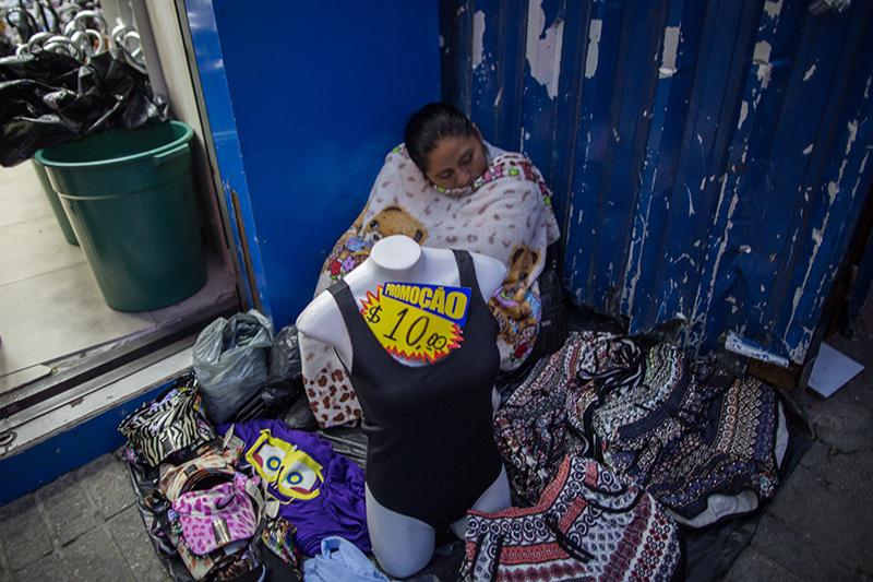 Imigrantes latino americanos fazem jornada dupla: durante o dia costuram, de madrugada vendem. É muito comum encontrar trabalhadores dormindo na feirinha. Foto: Flavio Forner/The Guardian